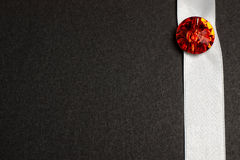Red stone on white ribbon on black Royalty Free Stock Photo