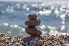 Red stones and pebbles stack, harmony and balance, one stone cairn on seacoast. Stability tower Royalty Free Stock Photos