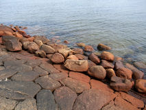 Red stones on the seashore. Red polluted stones on the sea coast Royalty Free Stock Images