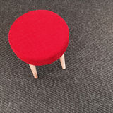 Red stool on gray carpet floor Royalty Free Stock Photography