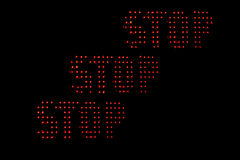 Red Stop over Black Background. Photograph with illuminated Word Stop repeated three times on a black background Royalty Free Stock Image