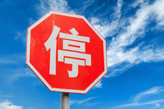 Red stop road sign with Chinese character. Above blue cloudy sky background Royalty Free Stock Photography