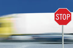 Red stop road sign motion blurred truck vehicle traffic background, regulatory warning signage octagon, white octagonal frame. Red stop road sign, motion blurred Royalty Free Stock Image