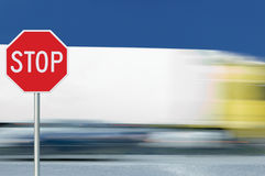 Red stop road sign, motion blurred truck vehicle traffic in background, regulatory warning signage octagon, white octagonal frame. Metallic pole post Stock Photos