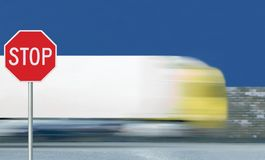 Red stop road sign, motion blurred truck vehicle traffic stock photography