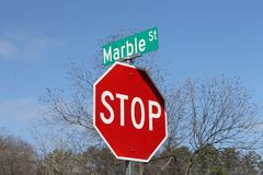 Red and stop sign and street name Stock Photography