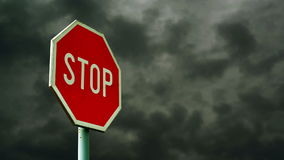 Red stop sign on the street. Roadside traffic sign for stopping with clouds time lapse footage in background. Stock Photography