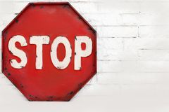 Red stop symbol on a white brick wall,  object. Symbols Royalty Free Stock Photography