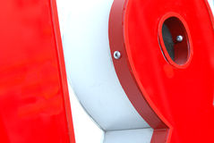 Red store plastic sign (detail). An element of a store sign with silver screws Stock Images