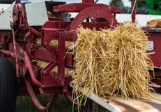 Red Straw Baler. Old but working straw baler pushing out a fresh bale of straw Stock Photography