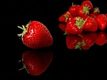 Red strawberries,  on a black reflective background. Red strawberries on a black reflective background front single strawberry in focus the rear strawberrys out Stock Images