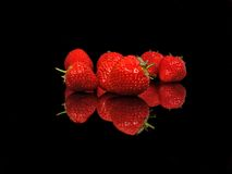 Red strawberries,  on a black reflective background Royalty Free Stock Images