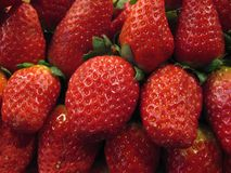 Red strawberries bunch. In a close up shot taken at the market (La Boqueria, Barcelona Stock Image
