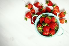 Red strawberries in colander on a white wooden table. Fresh red strawberries in a small colander on a white wooden table Royalty Free Stock Photo