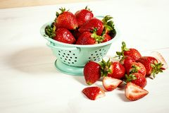 Red strawberries in colander on a white wooden table. Fresh red strawberries in a small colander on a white wooden table Royalty Free Stock Photography
