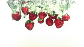 Red strawberries falling into water in super slow motion stock footage