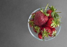 Red strawberries in a glass transparent bowl on a gray paper background. Horizontal banner, copy space. View from above stock images
