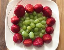 Red strawberries and green grapes Stock Images