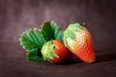 Red Strawberries and leaf with black stone background Royalty Free Stock Photo