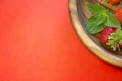 Red strawberries and a mint leaf in a wooden plate. Tasty strawberries and a mint leaf in a wooden plate on a red background. Top view cpmposition. Place for Royalty Free Stock Photos