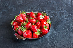 Red strawberries in a plate on concrete background. Ripe red strawberries in the iron plate on a dark concrete background Royalty Free Stock Images