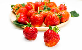 Red strawberries on plate. Isolated red strawberries on wooden plate Royalty Free Stock Image
