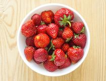 Red strawberries in plate isolated on wooden table Royalty Free Stock Photography