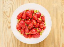 Red strawberries in plate isolated on wooden table Stock Photography