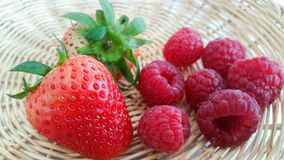 Red strawberries and raspberries. In basket stock photos