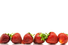 Red strawberries in a row. Red fresh strawberries isolated on white background Royalty Free Stock Photography