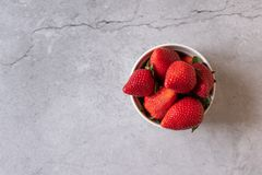 Red strawberries in a white cup on a wooden table stock photo