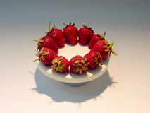 Red strawberries on white round plate studio shot Royalty Free Stock Photos