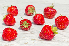 Red strawberries on a white wooden background Royalty Free Stock Image