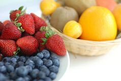 Red Strawberry, Blue Berry on White Plate Near Brown Woven Basket Royalty Free Stock Photo