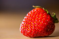 Red strawberry closeup on wooden table royalty free stock image