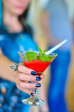 Red strawberry cocktail in hand of the girl is out of focus. Fruit cocktail in a glass. Blurring background. Strawberry smoothies. Royalty Free Stock Photography