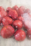 Red strawberry in drops of water and a cold rar in the defocus under the glass on a light wooden background Royalty Free Stock Photos