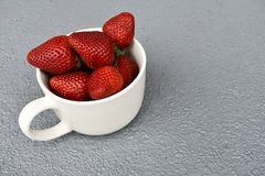White Cup Filled With Red Strawberries On A Grey Background stock photo