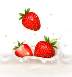 Red strawberry fruits falling into the milky splas Royalty Free Stock Image