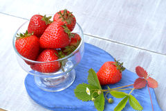 Red strawberry in glass dish on blue board - delicious snack in summer. Red, big strawberry in glass dish on blue, wooden board - delicious snack in summer Royalty Free Stock Photography