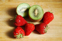 Strawberry and kiwi on chopping board Royalty Free Stock Photos