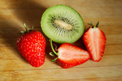 Strawberry and kiwi on chopping board Royalty Free Stock Photo