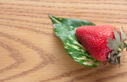 Red Strawberry Leaf. Green leaf and a red strawberry sitting on wood Stock Photos