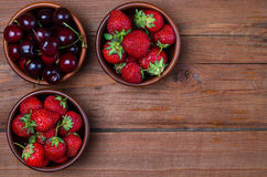 Red strawberry and ripe cherry on a wooden table, copy space. Royalty Free Stock Photography