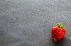 Red strawberry on slate background with copy space. Stock Photos