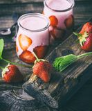 Red strawberry and two glass jars of smoothies. A ripe red strawberry and two glass jars of smoothies on a gray wooden table Royalty Free Stock Images
