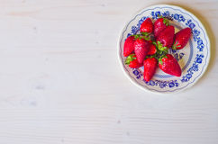 Red strawberry on white and blue plate Stock Photos