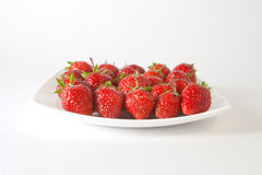 Red strawberry on white plate. On the white background Stock Images