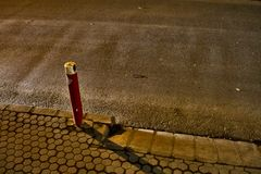 A red street pole and car lights sweeping the street. Showing asphalt texture and relief Stock Photo