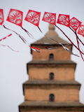 Red String of Kites with Pagoda in Background Royalty Free Stock Photo
